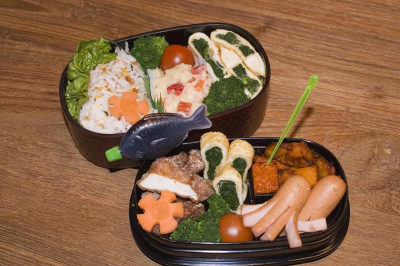 Oben: Reis mit Furikake (Streugewürz), Kartoffelsalat, Tomate und Brokkoli, Spinat-Tamagoyaki (Omelett). Unten: Chicken-Nuggets, restliches Spinat-Tamagoyaki, frittierter Kürbis, Oktopus-Würstchen