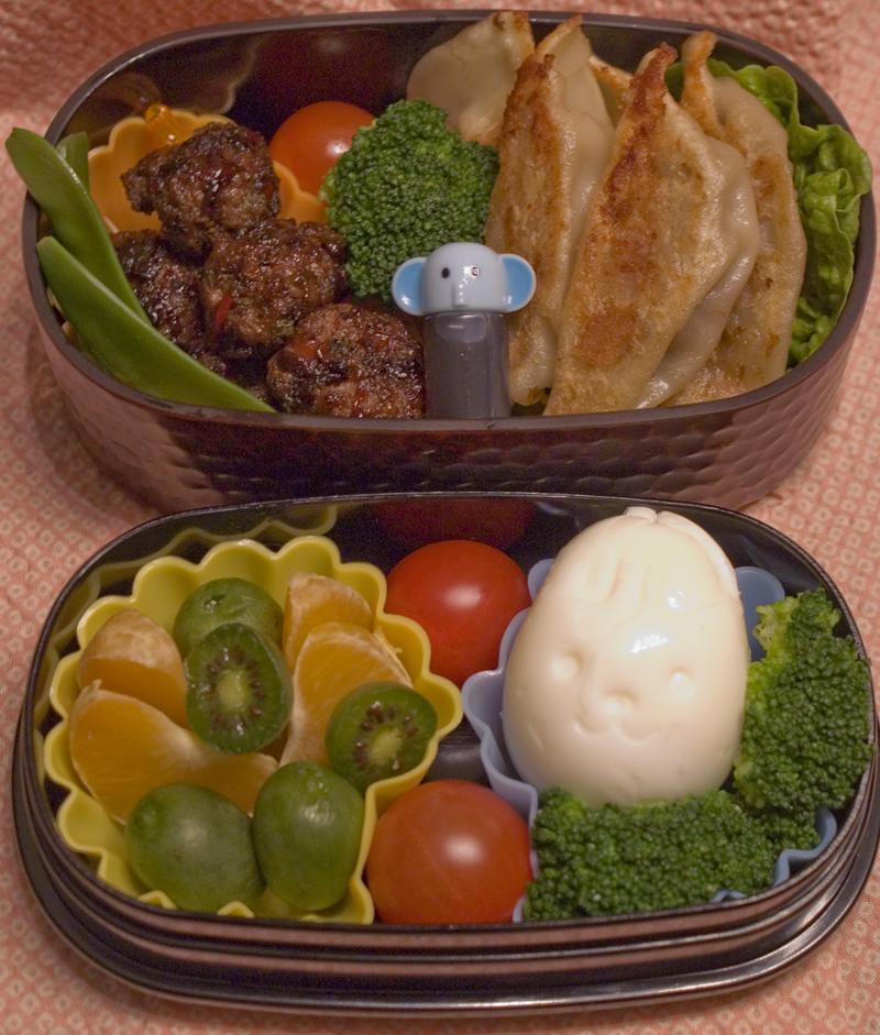 Oben: Zuckerschoten, Fleischbällchen, Gyoza (Teigtaschen), Sauce im Fläschchen. Unten: Mandarine und Kiwibeeren, Tomate, Ei in Hasenform, Brokkoli.