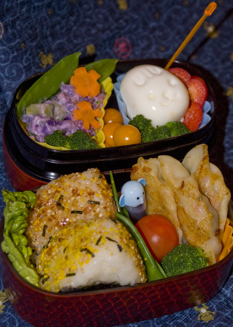 Oben: Zuckerschoten, lila Kartoffelsalat, Physalis, Ei in Hasenform, Paprikastreifen. Unten: Onigiri mit Furikake, Tomate, Brokkoli, Gyoza, Sauce im Fläschchen.