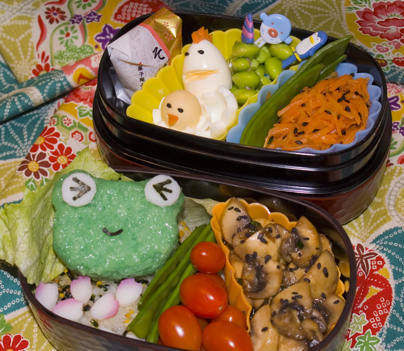 Oben: japanische Süßigkeit, Wachteleier, Edamame-Spieß, Zuckerschoten, Karottensalat. Unten: Onigiri auf Reis mit Furikake und Kamaboko, Zuckerschoten, Cherrytomaten, Champignons mit Saujasauce