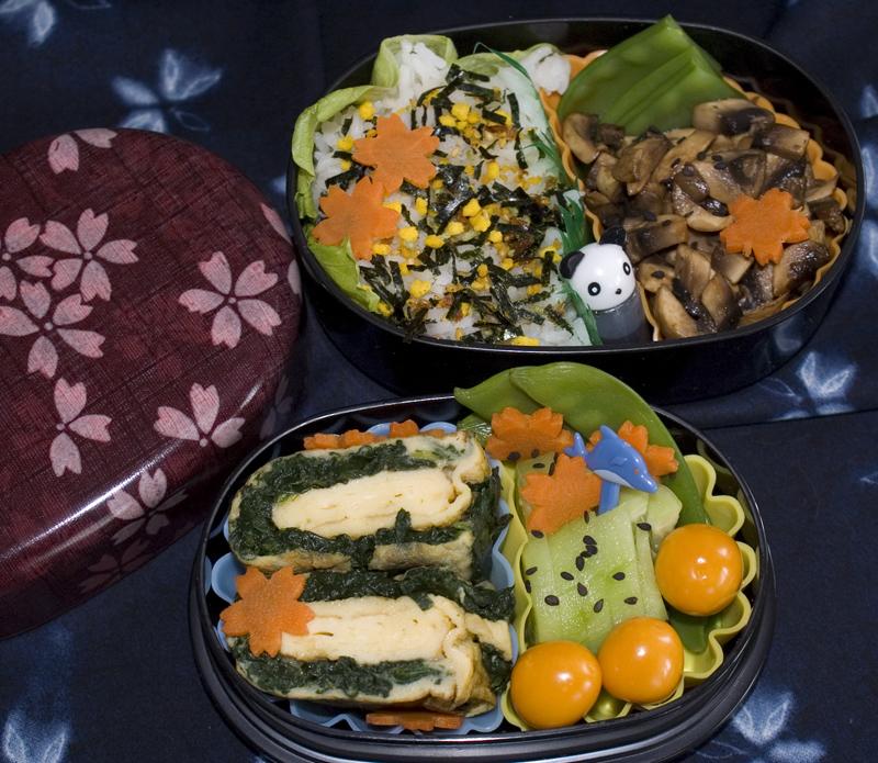 Oben: Reis mit Furikake, Champignons mit Sojasauce. Unten: Tamagoyaki mit Spinat, Gurken, Zuckerschoten und Karotte, Physalis.